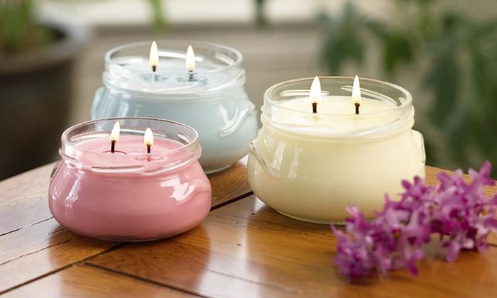 tre candele colorate in vasetti di vetro
